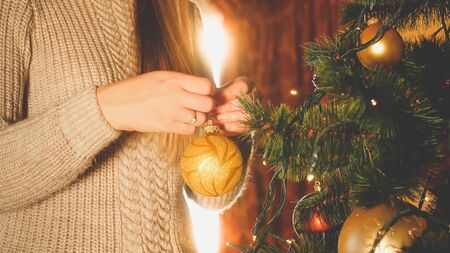 Closeup toned image of woman standing next to big window and decorating Christmas tree with baubles Banco de Imagens