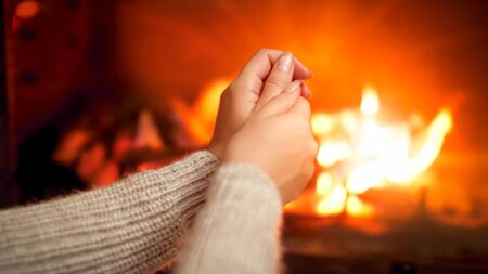Closeup photo of young wooman feeling cold sitting by the burning fire at house and rubbing freezing hands Фото со стока