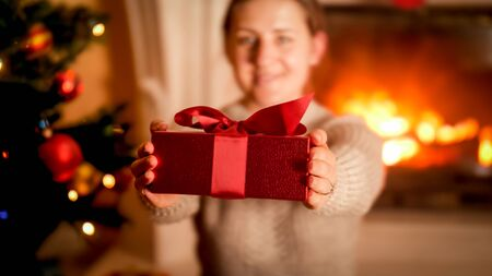 Closeup image of young woman showing red Christmas gift box in camera while sitting next to Xmas tree and burning fireplace
