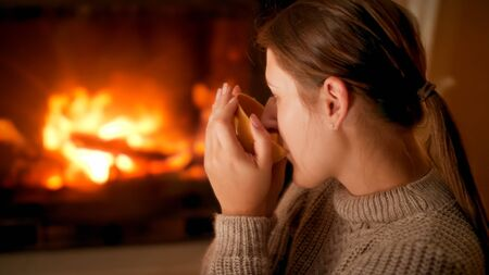 Portrait of young woman in sweater dirnking tea and enjoying burning fire in fireplace at home