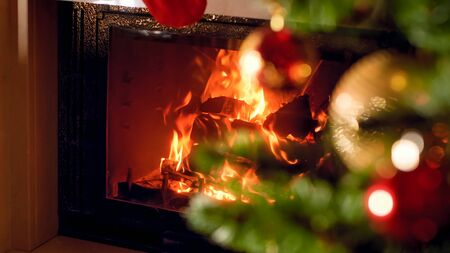 Christmas background of burning fireplace and decorated Xmas tree at house