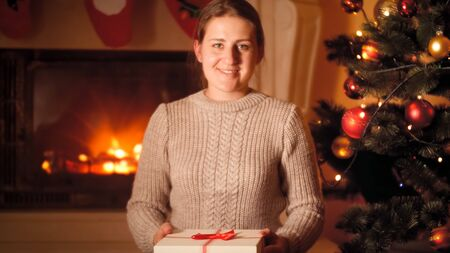Portrait of beautiful young woman in woolen sweater holding box with Christmas gift and looking in camera