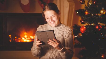 Toned portrait of happy smiling woman holding and using digital tablet on Christmas eve next to the fireplace