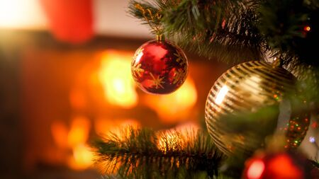 Closeup image of red and golden Xmas baubles hanging on Christmas tree aginst burning fire in fireplace 스톡 콘텐츠