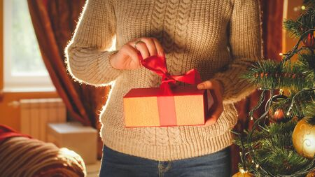 Toned photo of young woman unwrapping and opening Christmas gift box Reklamní fotografie