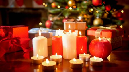 Closeup image of lots of burning candles and gifts against glowing Christmas tree at living room Stock Photo
