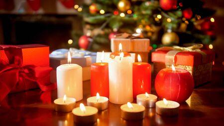 Image en gros plan de beaucoup de bougies allumées et de cadeaux contre un sapin de Noël rougeoyant dans le salon