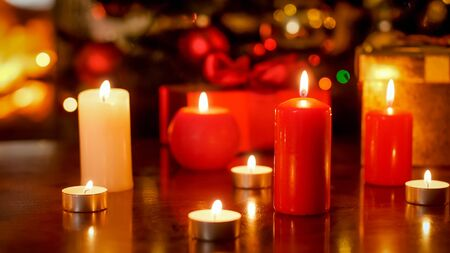 Closeup photo of lots of candles on wooden table decorated for Christmas eve
