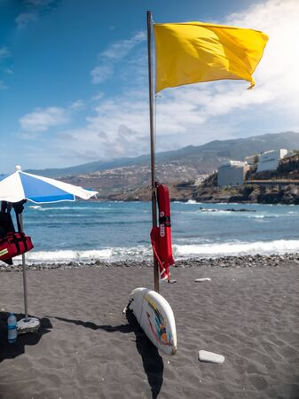 Photo of life rescue equipment on beach and warning yellow flag on black volcanic beach at ocean