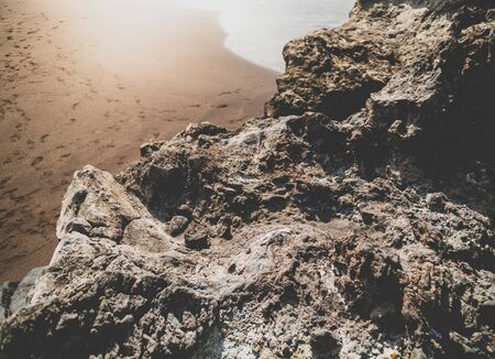 Closeup toned image of stone and cliffs on the sandy ocean beach
