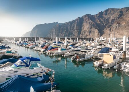 Beautiful photo of harbor with moored motorboats and yacht at Los Gigantes, Tenerife island