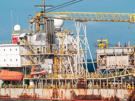 Toned photo of old rusty container cargo ship or oil tanker in docks Stock Photo