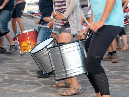Closeup photo of group of street musicians playing on drum during carnival or holiday
