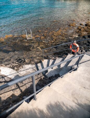 Beautiful image of descent to the ocean with stone stairs and metal railings