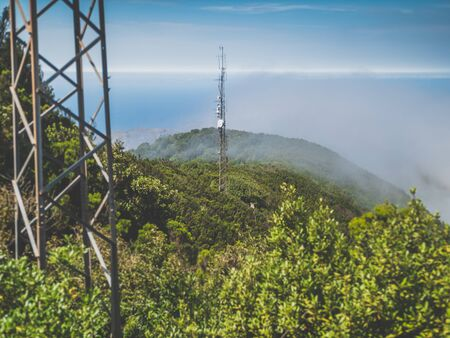 Toned image of communication signal towers and antennas in the jungle forest on mountain