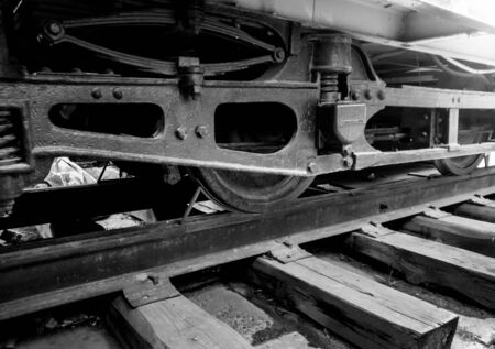 Closeup black and white image of old vintage tram wheels on rails