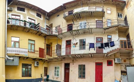 Toned panoramic image of inner court and facade of old living building at small european town