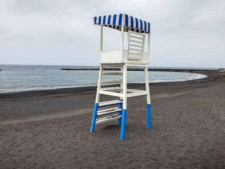 Image of wooden life rescue coast guard tower on the empty beach with black volcanic sand