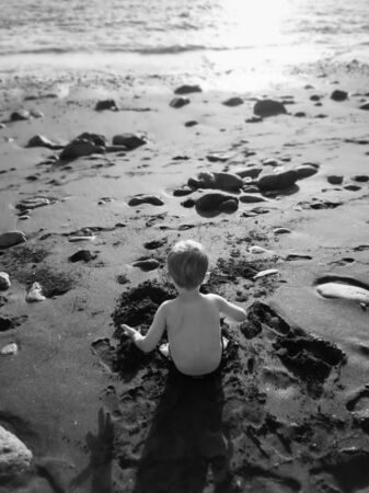 Black adn white rear view image of little boy sitting on beach sand and building castle Stockfoto