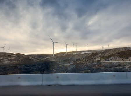Landscape of air wind turbines on the mountain hills at sunset light