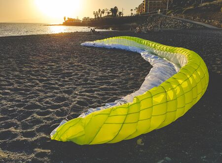 Toned photo of big parachute for paragliding lying on the sea beach at sunset