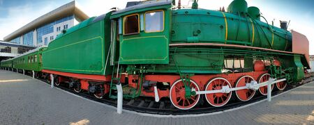 Panoramic image of old steam train at mdoern railway station
