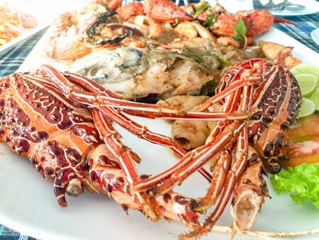 Closeup image of fresh cooked langoustines with vegetables on the dish at seafood restaurant