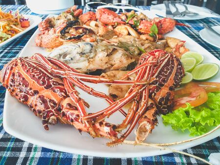 Toned food photo of prawn, langoustines, lobsters and squids on big dish at seafood restaurant Standard-Bild