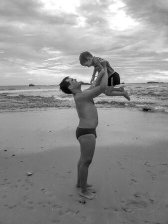 Black and white image of cheerful young father holding and throwing up hif laughing son the ocean beach