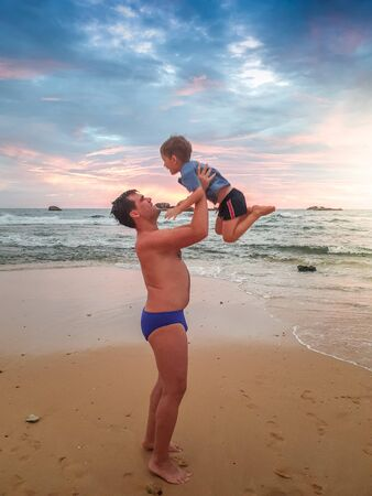 Photo of happy young father throwing up his son on ht eocean beach at sunset