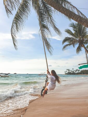 Toned photo of beautiful young wman swinging on the palm tree at beach