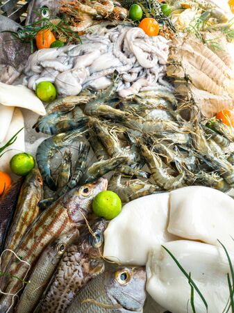 Closeup image of fresh fishes, shrimps, langoustine, octopus and lobster on the counter at seafood market Stock Photo