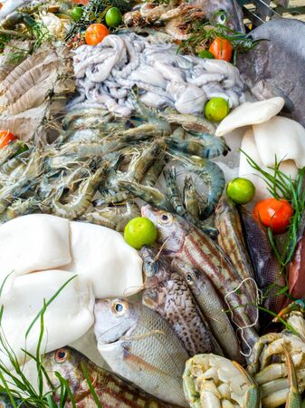 Closeup image of big assortment of fresh tasty uncooked seafood and vegetables on the market 版權商用圖片