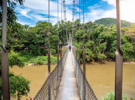 Beautiful photo of narrow old suspension bridge over the tropical river in Sri Lanka Stock Photo