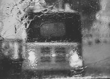 Black and white image of water rain droplets on window of tuk-tuk in Sri Lanka during heavy rain Stock Photo