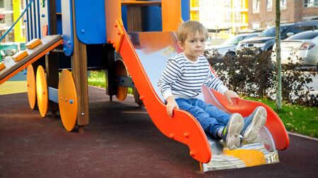 Upset little boy sitting on the slide at children playground Imagens