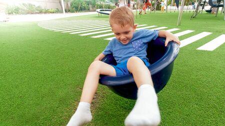 Portrait of cheerful smiling boy spinning in carousel on children playground at park Reklamní fotografie