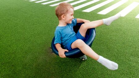 Happy smiling and laughing little boy sitting on rotating chair carousel on the playground