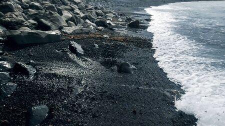 Landscape of black rocks and cliffs on volcanic sea beach Archivio Fotografico