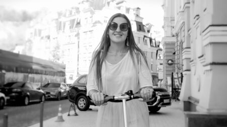 Black and white portrait of beautiful smiling woman in sunglasses riding on electric scooter on city street