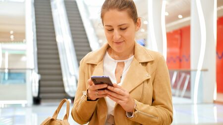 Portrait of young smiling woman using smartphone in big shopping mall