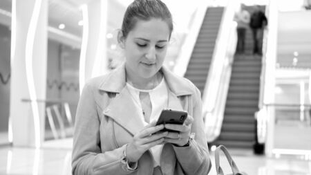 Black and white portrait of beautiful young woman in shopping mall browsing internet on smartphone