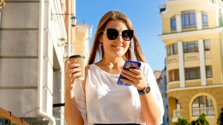 Portrait of beautiful smiling young woman holding cup of coffee walking on street and using smartphone