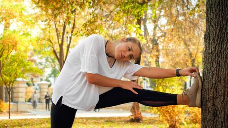 Beautiful young woman stretching and warming up before jogging in park at morning Imagens