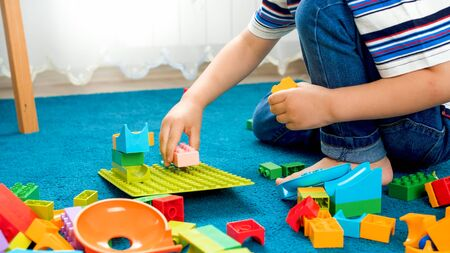 Closeup image of little boy sitting on floor and playing with toy blocks 写真素材