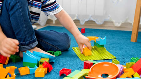 Closeup image of little boy assembling colorful toy constructor on carpet