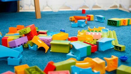 Closeup image of messy floor in playroom covered with colorful toy blocks