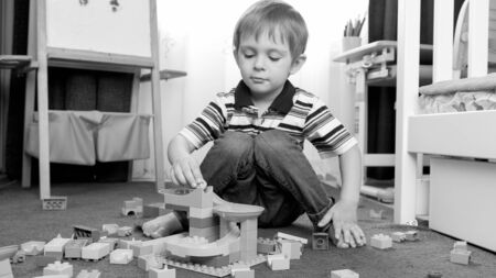 Black and white portrait of little toddler boy playing with constructor blocks and bricks on carpet at his room