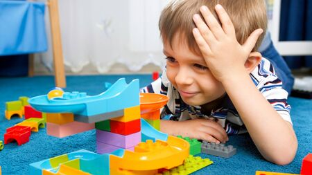 Portrait of happy smiling little boy lying on carpet at his room and looking on colorful toy constructor