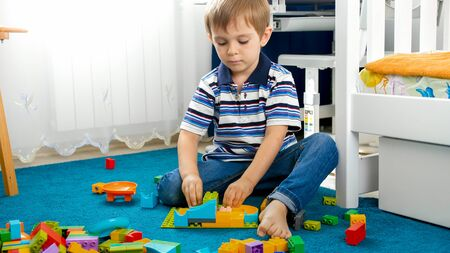 Portrait of little toddler boy sitting on floor in bedroom and playing with toy constructor